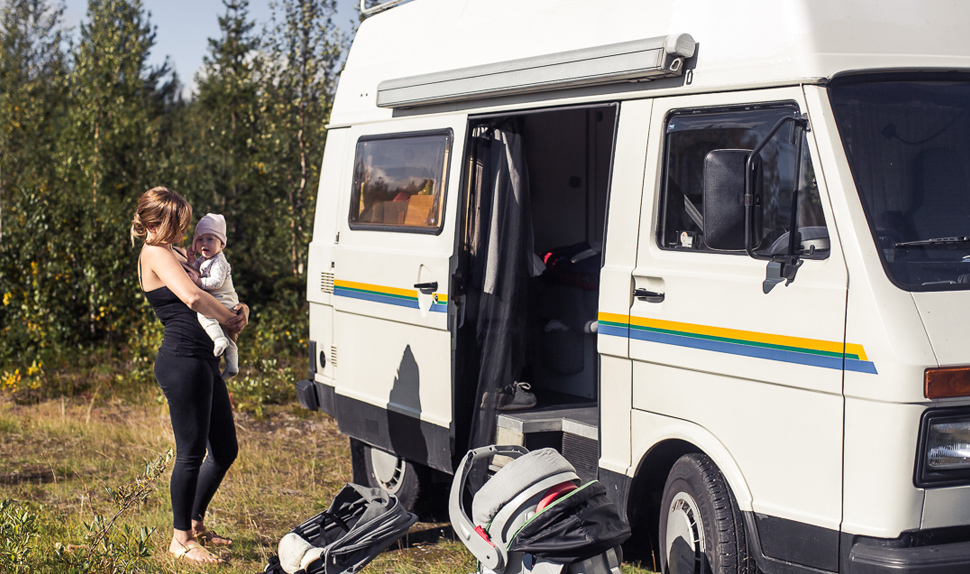 BABYBJÖRN Magazine for Parents – Mom Juli with one of the babies outside the camper van.